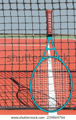 Modern graphite tennis racket resting on net and court white line. Outdoor red clay court and nylon rope net. Racket shape and net shadow in background. Vertical composition.  - stock photo