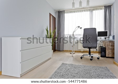 Modern grey home office with white commode, desk with computer and chair