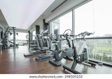 Modern gym interior with equipment and a beautiful view - stock photo