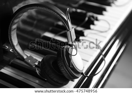 Modern headphones on piano keys