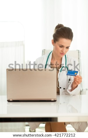 Modern health care. Female doctor with credit card shopping online while sitting at a desk in the office - stock photo