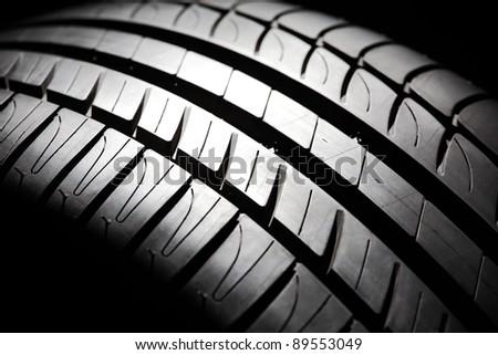 Modern high-performance sport summer tire close-up. Low key scene. - stock photo