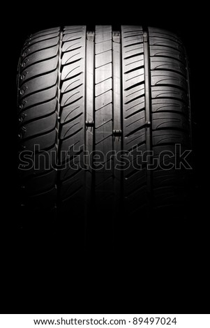 Modern high-performance sport summer tire isolated on a black background. Vertical composition. - stock photo