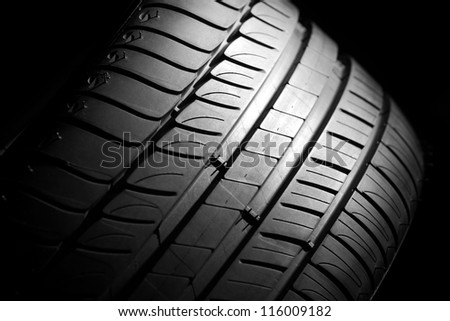 Modern high-performance sport summer tire on a black background. Low key scene. - stock photo