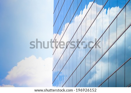modern high rise business building reflection with blue sky cloud - stock photo