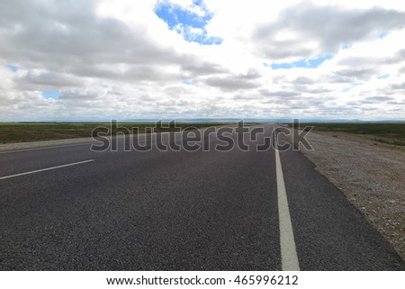 Modern highway across desert in the Western Kazakhstan against a cloudy sky