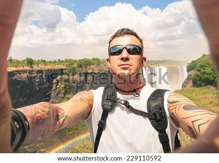 Modern hipster young man taking a selfie at Victoria Waterfalls - Adventure travel lifestyle enjoying moment of connection with nature - Trip excursion in Africa Zimbabwe nature wonder destination - stock photo