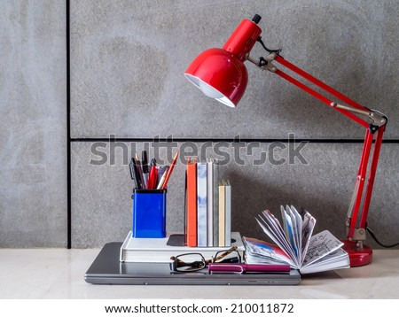 Modern home office desk with laptop and lamp - stock photo