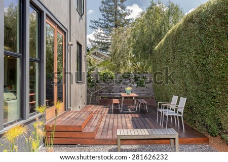 Modern home with large windows and amazing outside terrace with table and chairs. Green house with deck and zen garden. - stock photo
