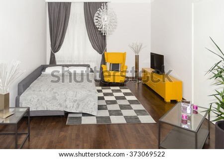 Modern Hotel Apartment with 3d Living Room and Bedroom Interior, White Walls. Luxury Livingroom with Sofa and Armchair in Corner. Room for Rent with Bed or Couch, Beautiful Curtain and Large Flat TV. - stock photo