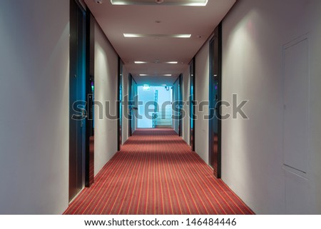 modern hotel corridor with red brown capet to exit stairway. - stock photo
