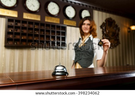 Modern hotel reception counter desk with bell. Hotel receptionist gives a card to a guest. Woman receptionist at desk unfocused. Selective focus at counter bell. Travel, hospitality concept.  - stock photo