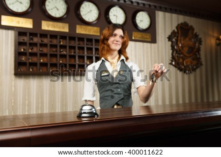Modern hotel reception counter desk with bell. Hotel receptionist gives keys to a guest. Woman receptionist at desk unfocused. Selective focus at counter bell. Travel, hospitality concept.  - stock photo