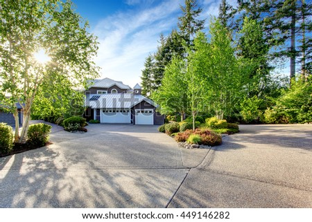 Modern house exterior with curb appeal. View of garage and spacious driveway with birch trees around. - stock photo