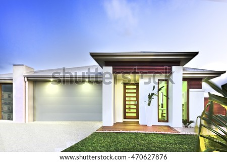 Modern house has a beautiful lawn in front of the house and garage from the left side that has concrete yard, lights are illuminated under the roof, There are wooden items attached to the walls