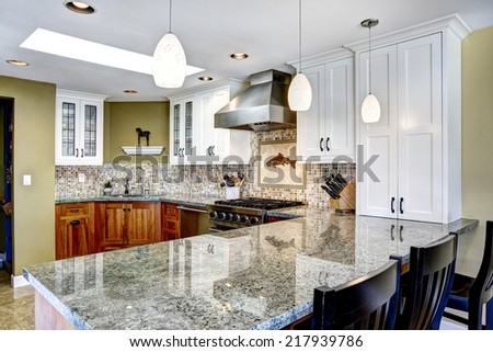 Modern house interior. White and brown kitchen room with shiny granite tops and mosaic back splash trim - stock photo