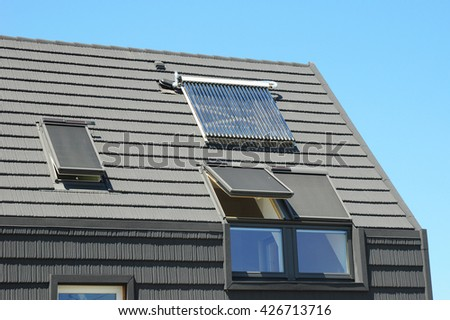 Modern House Roof with Solar Water Heater, Solar Panels and Skylights, Beautiful New Contemporary House with Solar Panels. Solar water panel heating. - stock photo