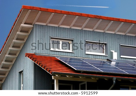 Modern house with solar panels (with blue sky and contrails)