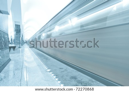 modern illuminated metro station with train motion - stock photo