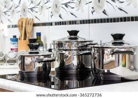 Modern induction cooker with the silver pots - stock photo