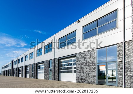 modern industrial units with loading doors and blue sky - stock photo