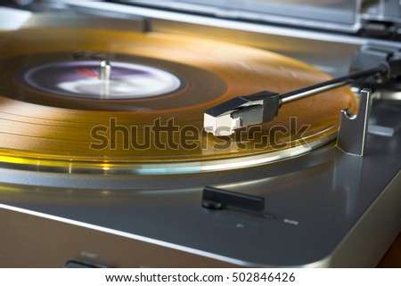 Modern, inexpensive turntable playing an orange colored vinyl record.