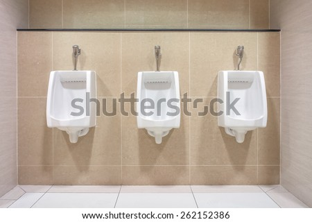 Modern interior design of white ceramic urinals for men in new toilet room - stock photo