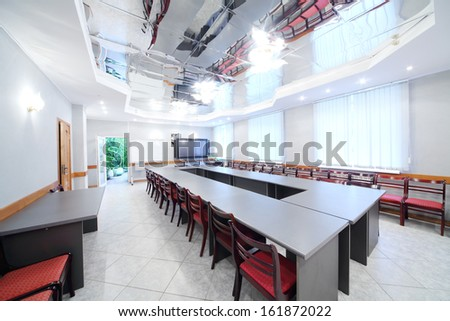 Modern interior of empty meeting room with conference table and red chairs - stock photo