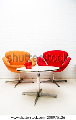 Modern interior table with coffee cup and two chairs.