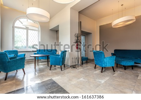 Modern interior with an original turquoise sofa and armchairs - stock photo