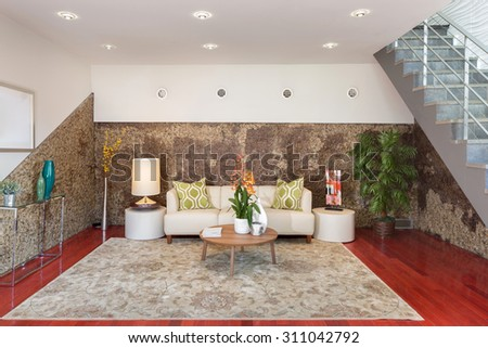 Modern interior with exposed walls, couch, rug arrangement and staircase - stock photo