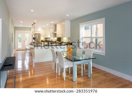 Modern interior with glass dining table, white designer chairs, beautiful wooden floor and open kitchen. - stock photo