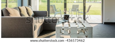Modern interior with sofa, stylish table and glass wall system, panorama
