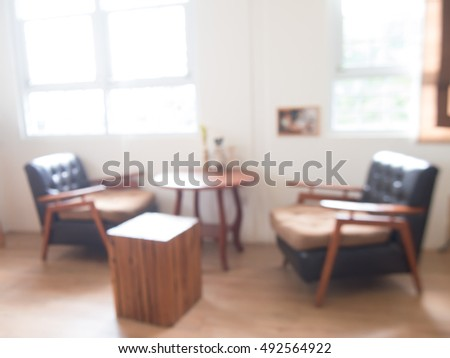 Modern interior with two armchairs near empty white wall of a small cafe, a blurred image.