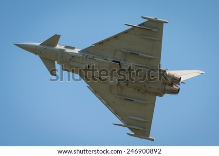 Modern jet fighter in flight as seen from underside - stock photo