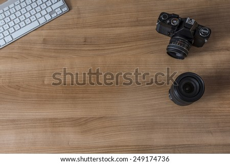 Modern keyboard and a vintage camera and a pen on a wooden desktop - stock photo