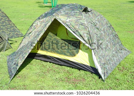 Modern khaki tent on green grass