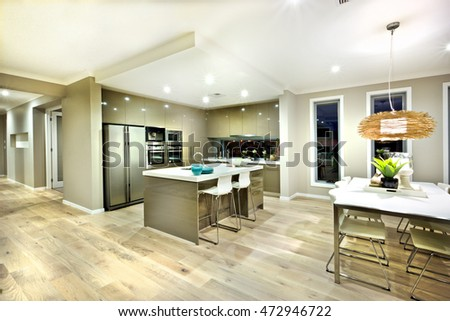 Modern kitchen and dinning area interior view of a modern house with lights on at night, there is a hanging lamp with a bamboo cover over the white table on the wooden floor hallway