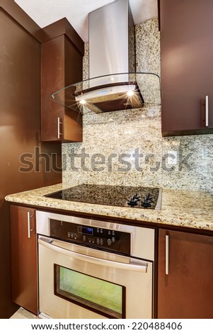 Modern kitchen appliance. Steel hood with glass element and lights on blend perfectly with steel stove with flat black shiny surface - stock photo
