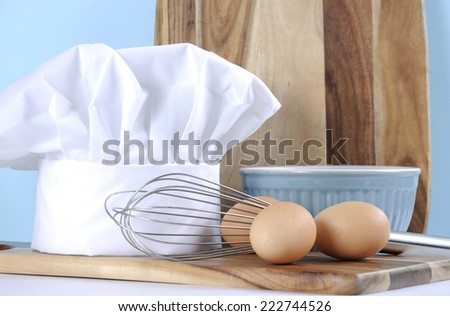 Modern kitchen cooking kitchenware and chef's hat with mixing bowl, whisk, chopping boards and eggs on a pale aqua blue and white background. Close up.
