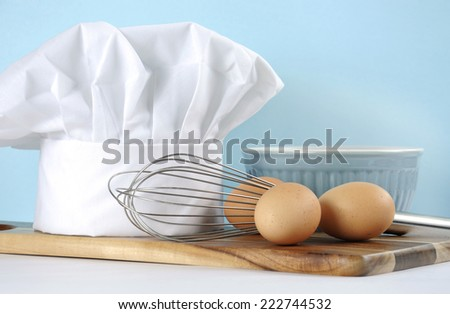 Modern kitchen cooking kitchenware and chef's hat with mixing bowl, whisk, chopping boards and eggs on a pale aqua blue and white background. Close up with copy space.