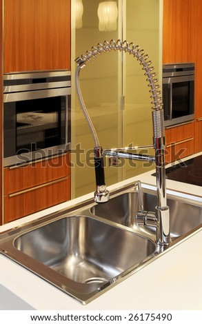 Modern kitchen faucet with oven in background