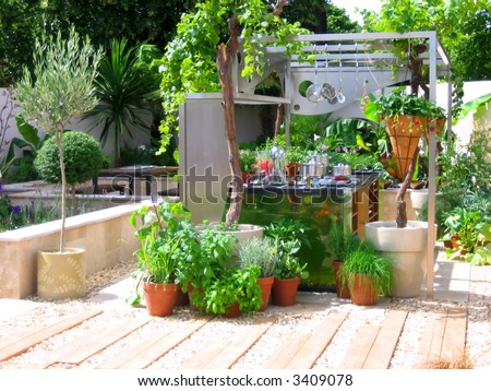 Modern kitchen in the garden with fresh green plants - stock photo