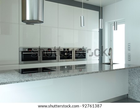 Modern kitchen in white and grey with granite countertop and built-in appliances - stock photo