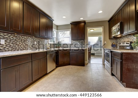 Modern kitchen interior with dark brown storage cabinets with granite counter tops and new tile floor - stock photo
