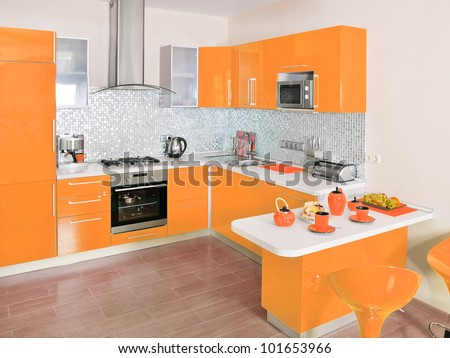Modern kitchen interior with orange decoration - stock photo