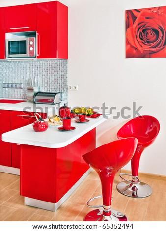Modern kitchen interior with red decoration - stock photo