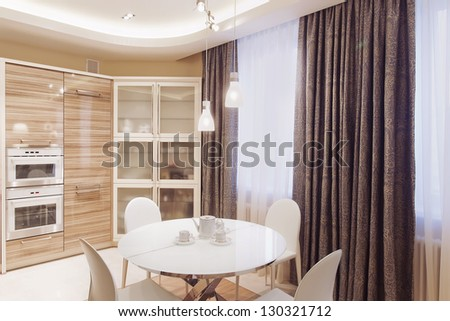 Modern kitchen interior with white dining table and four chairs - stock photo