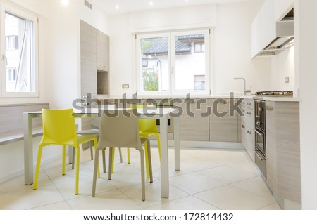 Modern kitchen interior with wooden cabinets, white table, grey and yellow chairs - stock photo