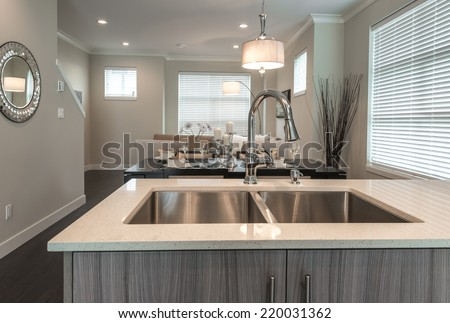 Modern kitchen sink and the living room at the back in a brand new house. Interior design. - stock photo